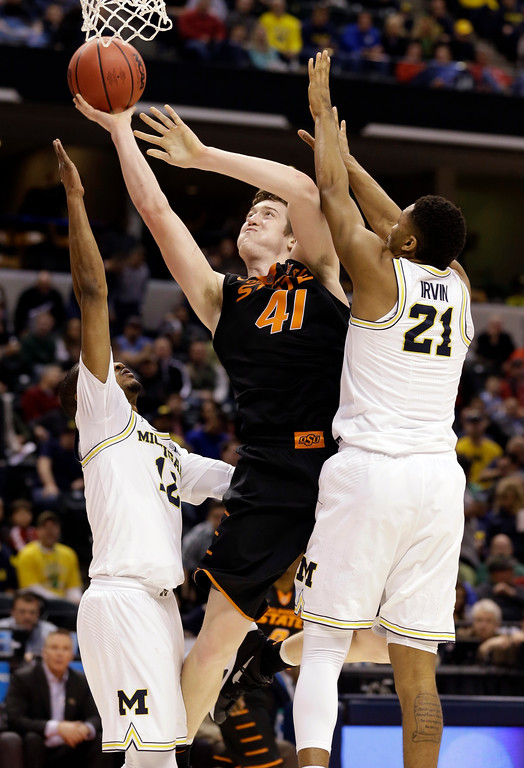 . Oklahoma State forward Mitchell Solomon (41) shoots between Michigan guard Zak Irvin (21) and guard Muhammad-Ali Abdur-Rahkman (12) during the second half of a first-round game in the men\'s NCAA college basketball tournament in Indianapolis, Friday, March 17, 2017. Michigan defeated Oklahoma State 92-91. (AP Photo/Michael Conroy)