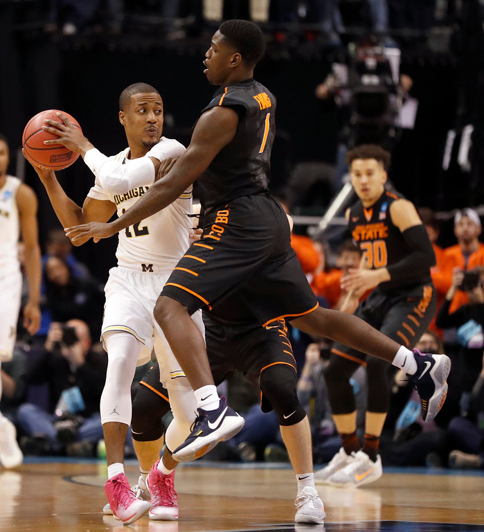 . Michigan\'s Muhammad-Ali Abdur-Rahkman, left, looks to pass as Oklahoma State\'s Jawun Evans defends during the first half of a first-round game in the men\'s NCAA college basketball tournament Friday, March 17, 2017, in Indianapolis, Mo. (AP Photo/Jeff Roberson)
