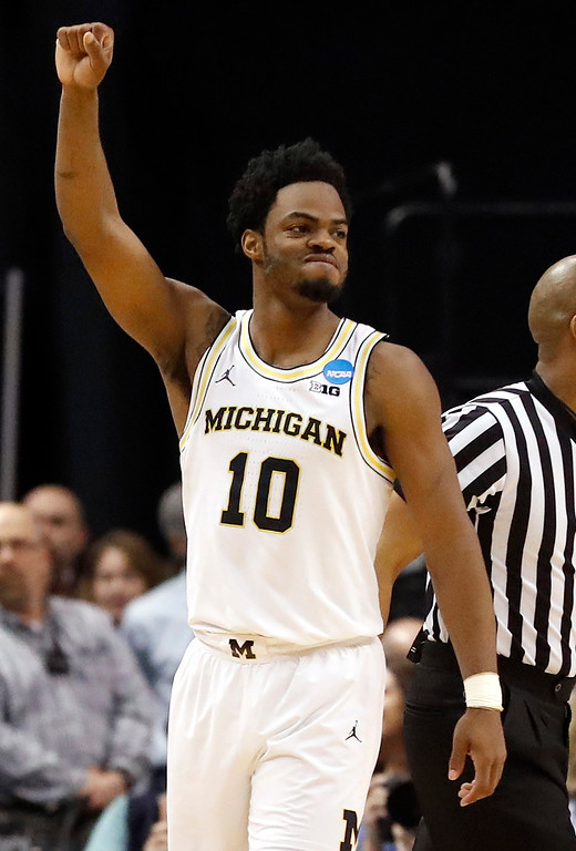 . Michigan\'s Derrick Walton Jr. celebrates as the buzzer sounds at the end of a first-round game against Oklahoma State in the men\'s NCAA college basketball tournament Friday, March 17, 2017, in Indianapolis, Mo. Michigan won 92-91. (AP Photo/Jeff Roberson)