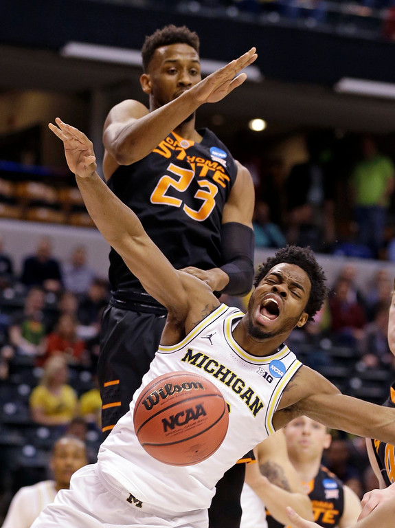 . Oklahoma State forward Leyton Hammonds (23) blocks the shot of Michigan guard Derrick Walton Jr. (10) during a first-round game in the men\'s NCAA college basketball tournament in Indianapolis, Friday, March 17, 2017. (AP Photo/Michael Conroy)