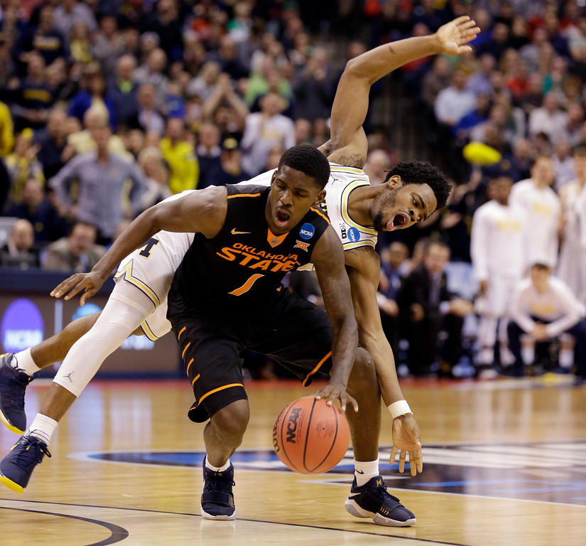 . Michigan guard Derrick Walton Jr. (10) fouls Oklahoma State guard Jawun Evans (1) from behind during the second half of a first-round game in the men\'s NCAA college basketball tournament in Indianapolis, Friday, March 17, 2017. Michigan defeated Oklahoma State 92-91. (AP Photo/Michael Conroy)