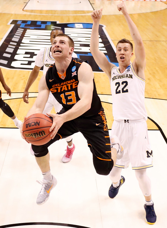 . Oklahoma State\'s Phil Forte III, left, heads to the basket as Michigan\'s Duncan Robinson watches during the first half of a first-round game in the men\'s NCAA college basketball tournament Friday, March 17, 2017, in Indianapolis, Mo. (AP Photo/Jeff Roberson)
