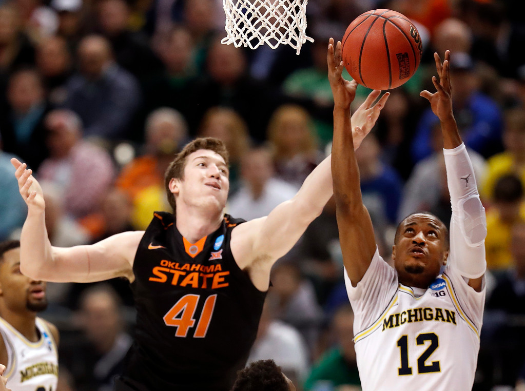 . Oklahoma State\'s Mitchell Solomon (41) and Michigan\'s Muhammad-Ali Abdur-Rahkman reach for the ball during the second half of a first-round game in the men\'s NCAA college basketball tournament Friday, March 17, 2017, in Indianapolis, Mo. Michigan won 92-91. (AP Photo/Jeff Roberson)