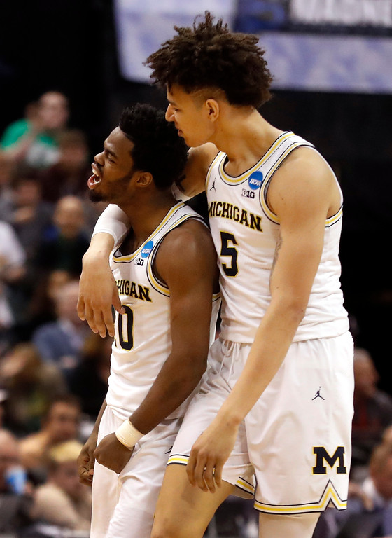 . Michigan\'s Derrick Walton Jr., left, and teammate D.J. Wilson celebrate during the second half of a first-round game against Oklahoma State in the men\'s NCAA college basketball tournament Friday, March 17, 2017, in Indianapolis, Mo. Michigan won 92-91. (AP Photo/Jeff Roberson)