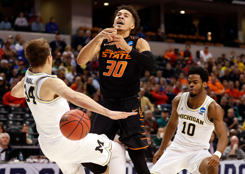 . Oklahoma State\'s Jeffrey Carroll (30) loses control of the ball is fouled on his way to the basket by Michigan\'s Mark Donnal (34) as Derrick Walton Jr. (10) watches during the first half of a first-round game in the men\'s NCAA college basketball tournament Friday, March 17, 2017, in Indianapolis, Mo. (AP Photo/Jeff Roberson)