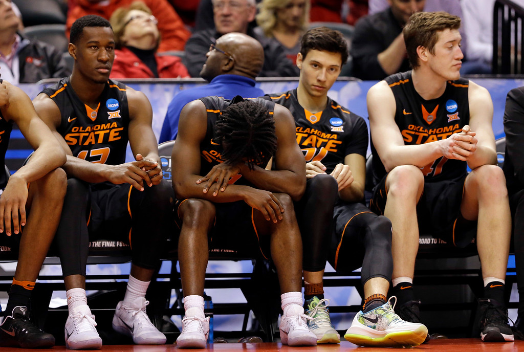. Oklahoma State guard Brandon Averette (0), left center, covers his head late in the second half of a first-round game against Michigan in the men\'s NCAA college basketball tournament in Indianapolis, Friday, March 17, 2017. Michigan defeated Oklahoma State 92-91. (AP Photo/Michael Conroy)