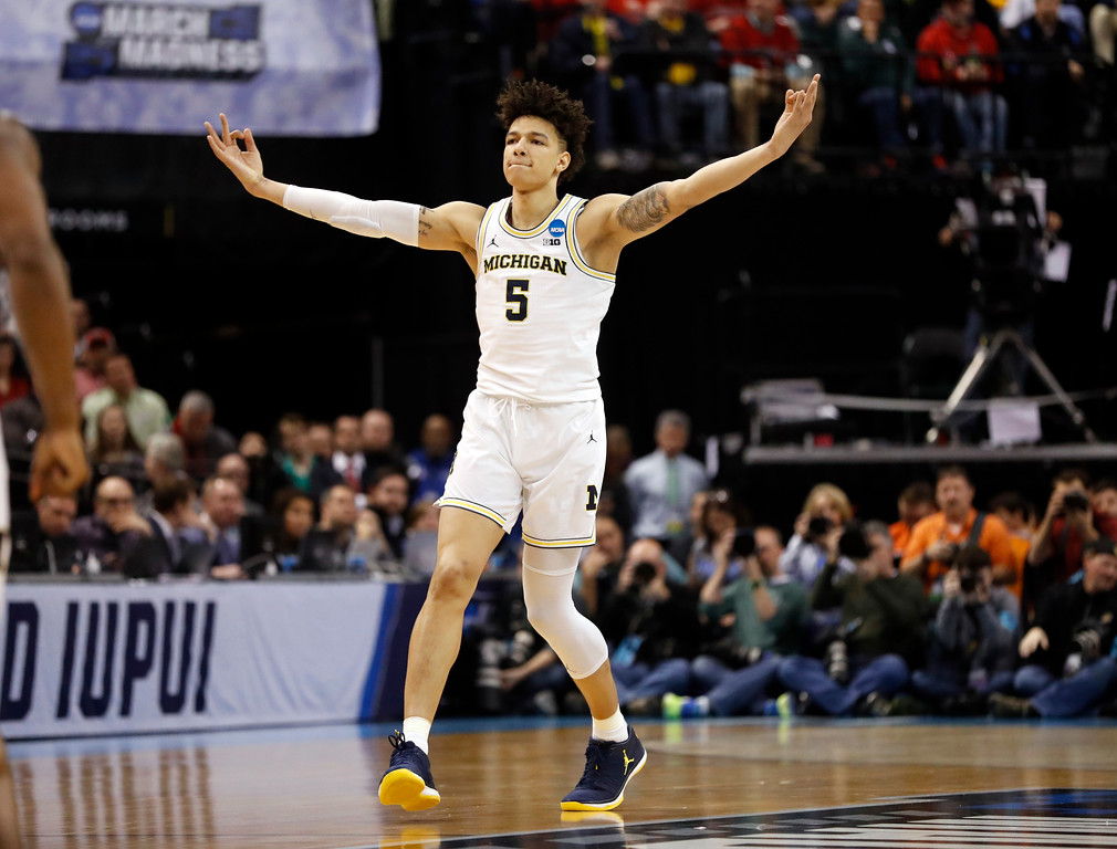 . Michigan\'s D.J. Wilson celebrates after hitting a 3-point basket during the first half of a first-round game against Oklahoma State in the men\'s NCAA college basketball tournament Friday, March 17, 2017, in Indianapolis, Mo. Michigan won 92-91. (AP Photo/Jeff Roberson)