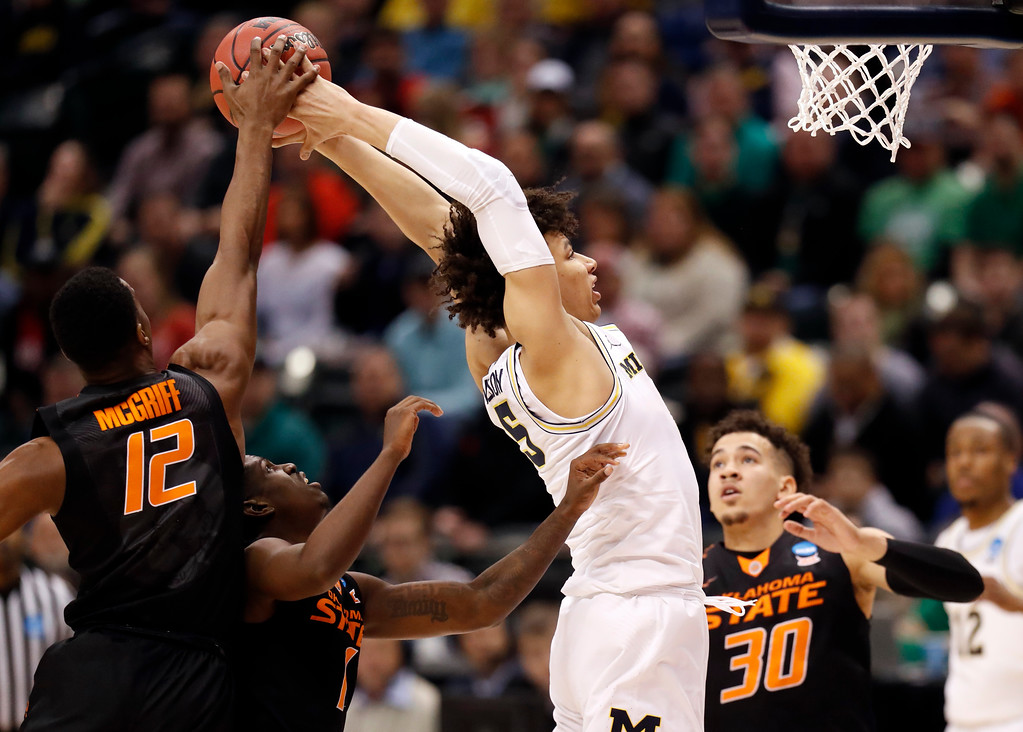 . Michigan\'s D.J. Wilson (5) heads to the basket as the ball is knocked away by Oklahoma State\'s Cameron McGriff (12) and Oklahoma State\'s Jawun Evans and Jeffrey Carroll (30) watch during the first half of a first-round game in the men\'s NCAA college basketball tournament Friday, March 17, 2017, in Indianapolis, Mo. (AP Photo/Jeff Roberson)