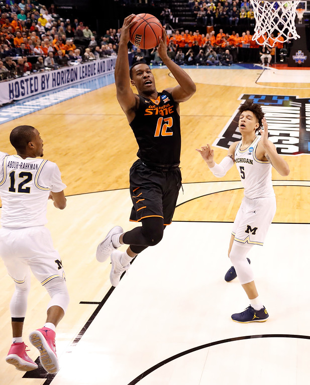 . Oklahoma State\'s Cameron McGriff, center, heads to the basket as Michigan\'s Muhammad-Ali Abdur-Rahkman, left, and D.J. Wilson, right, defend during the first half of a first-round game in the men\'s NCAA college basketball tournament Friday, March 17, 2017, in Indianapolis, Mo. (AP Photo/Jeff Roberson)
