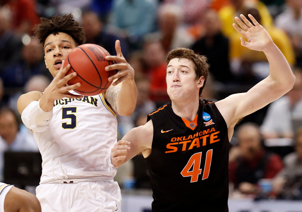 . Michigan\'s D.J. Wilson (5) grabs a rebound as Oklahoma State\'s Mitchell Solomon watches during the second half of a first-round game in the men\'s NCAA college basketball tournament Friday, March 17, 2017, in Indianapolis, Mo. Michigan won 92-91. (AP Photo/Jeff Roberson)