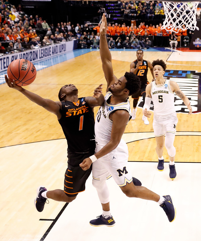 . Oklahoma State\'s Jawun Evans (1) is fouled on his way to the basket by Michigan\'s Derrick Walton Jr. as Michigan\'s D.J. Wilson (5) and Oklahoma State\'s Cameron McGriff (12) watch during the first half of a first-round game in the men\'s NCAA college basketball tournament Friday, March 17, 2017, in Indianapolis, Mo. (AP Photo/Jeff Roberson)