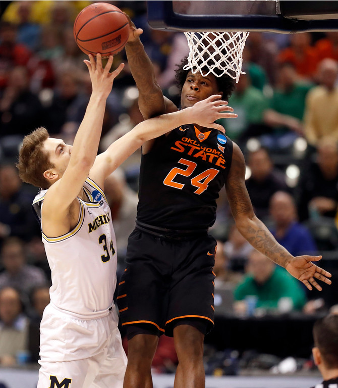 . Oklahoma State\'s Davon Dillard (24) knocks away a shot by Michigan\'s Mark Donnal during the first half of a first-round game in the men\'s NCAA college basketball tournament Friday, March 17, 2017, in Indianapolis, Mo. (AP Photo/Jeff Roberson)