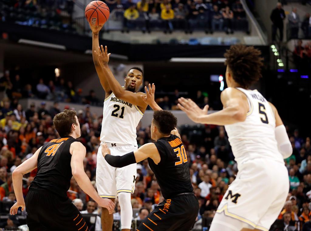 . Michigan\'s Zak Irvin (21) passes to teammate D.J. Wilson, right, as Oklahoma State\'s Mitchell Solomon, left, and Jeffrey Carroll (30) defend during the first half of a first-round game in the men\'s NCAA college basketball tournament Friday, March 17, 2017, in Indianapolis, Mo. Michigan won 92-91. (AP Photo/Jeff Roberson)