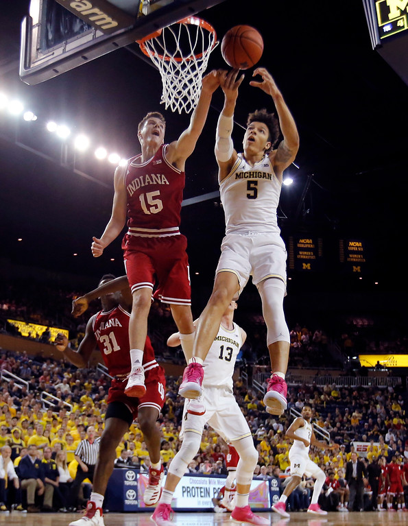 . Indiana guard Zach McRoberts (15) and Michigan forward D.J. Wilson (5) reach for the rebound during the first half of an NCAA college basketball game, Thursday, Jan. 26, 2017, in Ann Arbor, Mich. (AP Photo/Carlos Osorio)