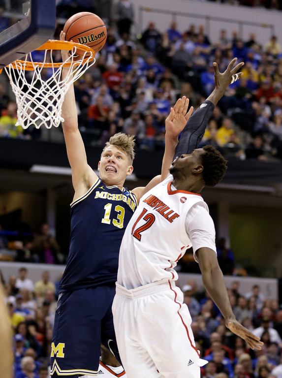 . Michigan forward Moritz Wagner (13) shoots over Louisville forward Mangok Mathiang (12) during the second half of a second-round game in the men�s NCAA college basketball tournament in Indianapolis, Sunday, March 19, 2017. Michigan defeated Louisville 73-69. (AP Photo/Michael Conroy)