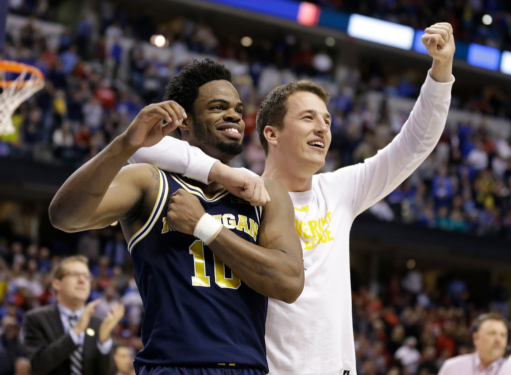 . Michigan guard Derrick Walton Jr. (10) and guard Andrew Dakich (11) celebrate following a 73-69 win over Louisville in a second-round game in the men�s NCAA college basketball tournament in Indianapolis, Sunday, March 19, 2017.  (AP Photo/Michael Conroy)