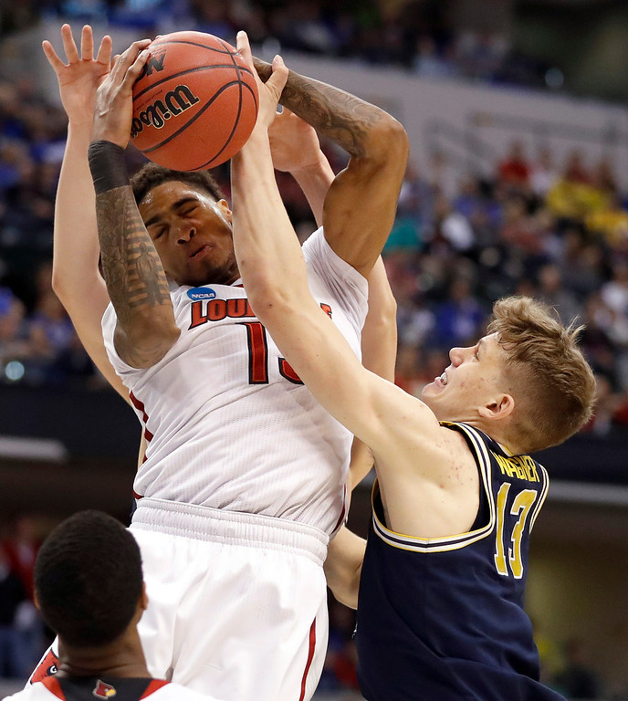 . Louisville\'s Ray Spalding, left, and Michigan\'s Moritz Wagner reach for a rebound during the first half of a second-round game in the men\'s NCAA college basketball tournament Sunday, March 19, 2017, in Indianapolis. (AP Photo/Jeff Roberson)