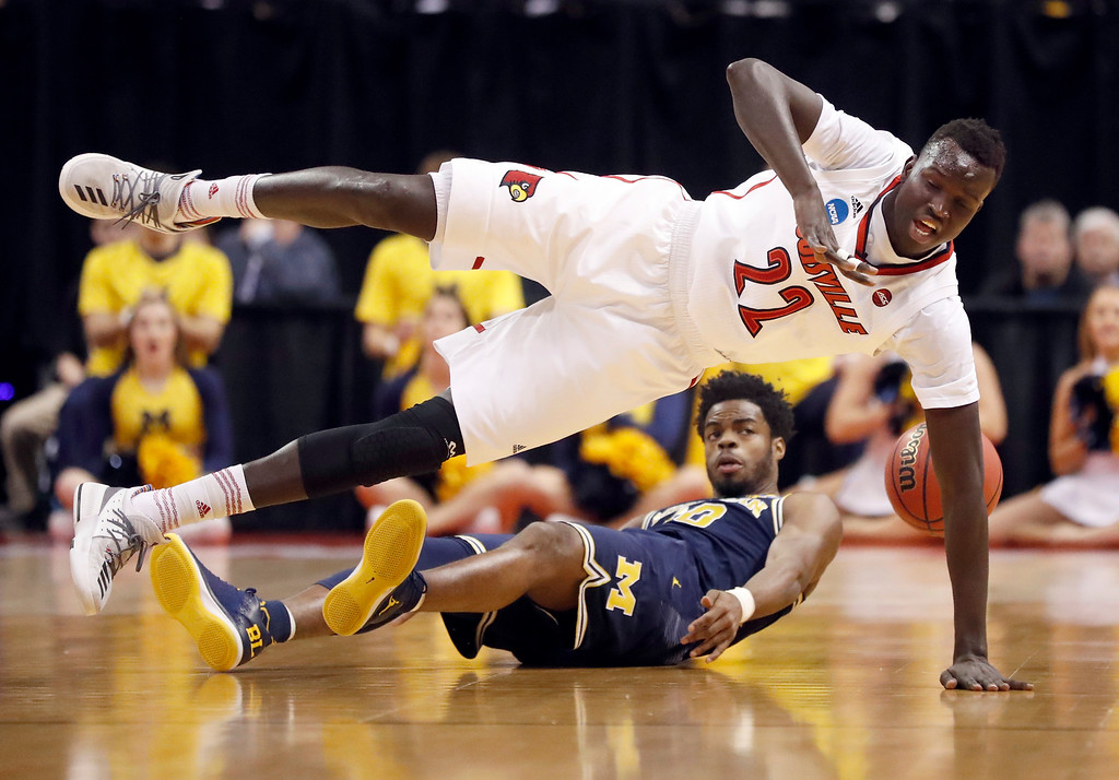 . Louisville\'s Deng Adel (22) loses control of the ball after colliding with Michigan\'s Derrick Walton Jr. (10) during the first half of a second-round game in the men\'s NCAA college basketball tournament Sunday, March 19, 2017, in Indianapolis. (AP Photo/Jeff Roberson)