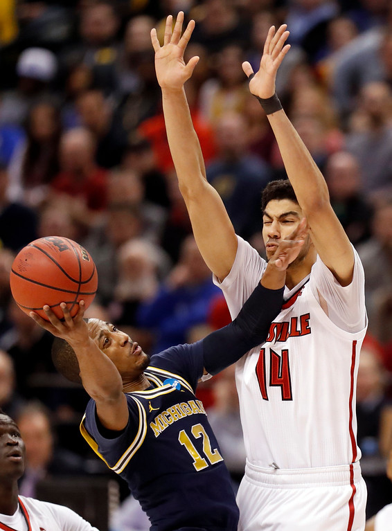 . Michigan\'s Muhammad-Ali Abdur-Rahkman (12) heads to the basket as Louisville\'s Anas Mahmoud (14) defends during the second half of a second-round game in the men\'s NCAA college basketball tournament Sunday, March 19, 2017, in Indianapolis. Michigan won 73-69. (AP Photo/Jeff Roberson)