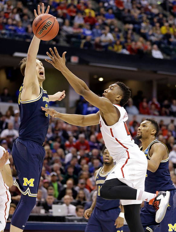 . Michigan forward Mark Donnal (34) blocks the shot of Louisville guard Donovan Mitchell (45) during the first half of a second-round game in the men�s NCAA college basketball tournament in Indianapolis, Sunday, March 19, 2017. (AP Photo/Michael Conroy)