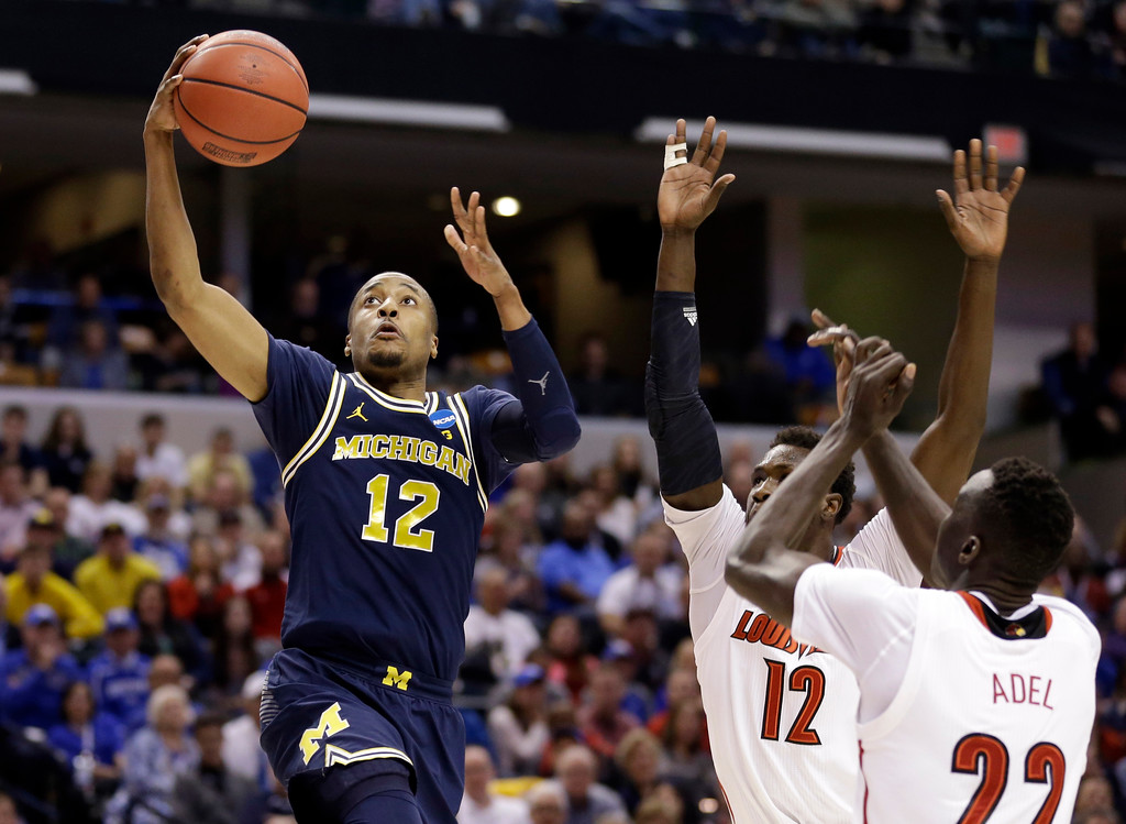 . Michigan guard Muhammad-Ali Abdur-Rahkman (12) shoots over Louisville forward Mangok Mathiang (12) and forward Deng Adel (22) during the second half of a second-round game in the men�s NCAA college basketball tournament in Indianapolis, Sunday, March 19, 2017. Michigan defeated Louisville 73-69. (AP Photo/Michael Conroy)