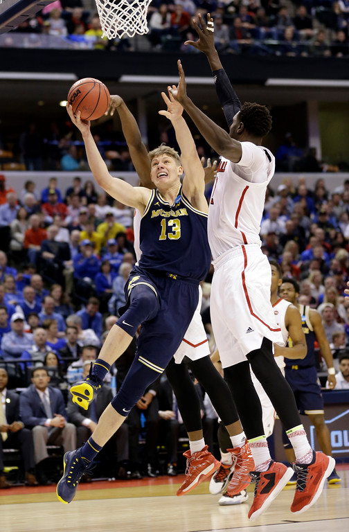 . Michigan forward Moritz Wagner (13) is fouled by Louisville forward Deng Adel (22) as he shoots during the second half of a second-round game in the men�s NCAA college basketball tournament in Indianapolis, Sunday, March 19, 2017. Michigan defeated Louisville 73-69. (AP Photo/Michael Conroy)