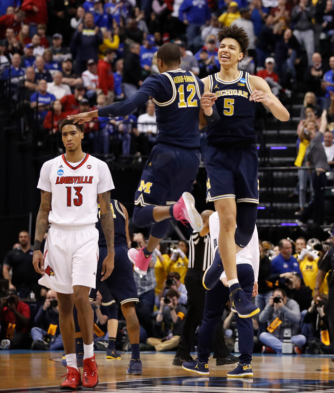 . Michigan\'s D.J. Wilson (5) and teammate Muhammad-Ali Abdur-Rahkman (12) celebrate as Louisville\'s Ray Spalding (13) walks past following a second-round game in the men\'s NCAA college basketball tournament Sunday, March 19, 2017, in Indianapolis. Michigan won 73-69. (AP Photo/Jeff Roberson)