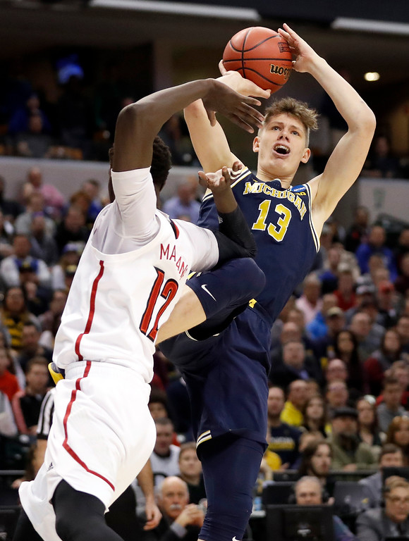 . Michigan\'s Moritz Wagner (13) shoots over Louisville\'s Mangok Mathiang (12) during the first half of a second-round game in the men\'s NCAA college basketball tournament Sunday, March 19, 2017, in Indianapolis. (AP Photo/Jeff Roberson)