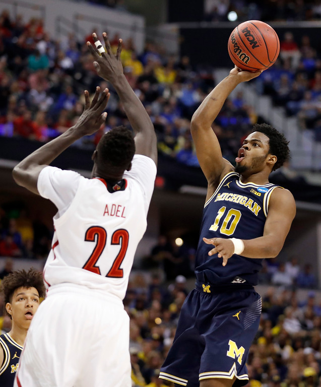 . Michigan\'s Derrick Walton Jr. (10) shoots over Louisville\'s Deng Adel during the first half of a second-round game in the men\'s NCAA college basketball tournament Sunday, March 19, 2017, in Indianapolis. (AP Photo/Jeff Roberson)