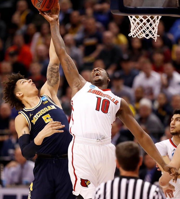 . Michigan\'s D.J. Wilson (5) and Louisville\'s Jaylen Johnson (10) reach for a rebound during the first half of a second-round game in the men\'s NCAA college basketball tournament Sunday, March 19, 2017, in Indianapolis. (AP Photo/Jeff Roberson)
