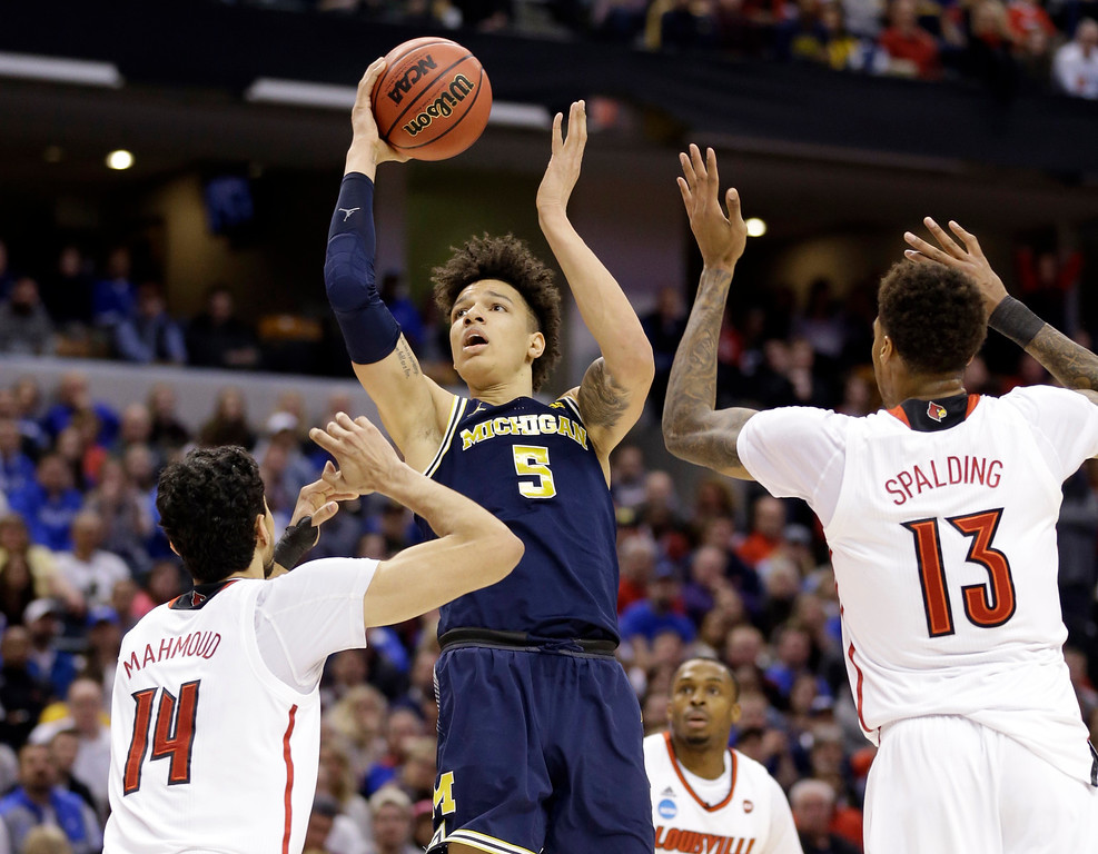 . Michigan forward D.J. Wilson (5) shoots over Louisville forward Anas Mahmoud (14) and forward Ray Spalding (13) during the second half of a second-round game in the men�s NCAA college basketball tournament in Indianapolis, Sunday, March 19, 2017. Michigan defeated Louisville 73-69. (AP Photo/Michael Conroy)