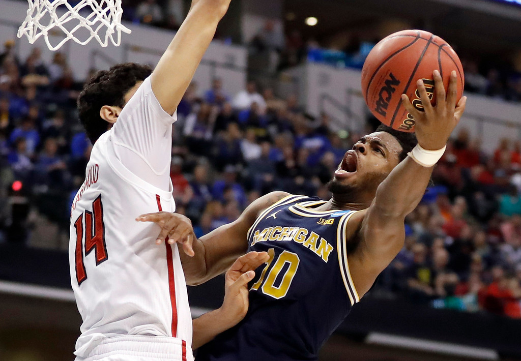 . Michigan\'s Derrick Walton Jr. (10) heads to the basket as Louisville\'s Anas Mahmoud defends during the first half of a second-round game in the men\'s NCAA college basketball tournament Sunday, March 19, 2017, in Indianapolis. (AP Photo/Jeff Roberson)