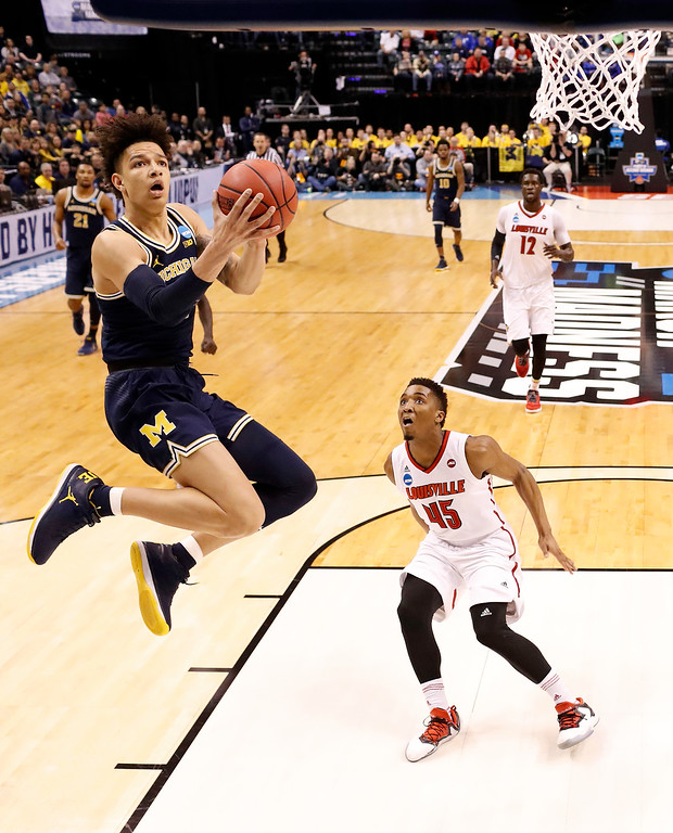 . Michigan\'s D.J. Wilson, left, heads to the basket as Louisville\'s Donovan Mitchell (45) watches during the first half of a second-round game in the men\'s NCAA college basketball tournament Sunday, March 19, 2017, in Indianapolis. (AP Photo/Jeff Roberson)