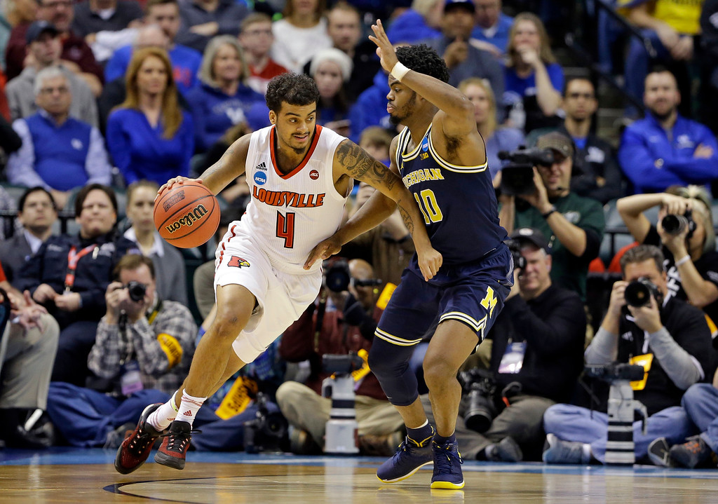 . Louisville guard Quentin Snider (4) drives on Michigan guard Derrick Walton Jr. (10) during the second half of a second-round game in the men�s NCAA college basketball tournament in Indianapolis, Sunday, March 19, 2017. Michigan defeated Louisville 73-69. (AP Photo/Michael Conroy)