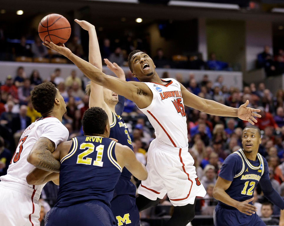 . Louisville guard Donovan Mitchell (45) lays in a shot over Michigan guard Zak Irvin (21) during the first half of a second-round game in the men�s NCAA college basketball tournament in Indianapolis, Sunday, March 19, 2017. (AP Photo/Michael Conroy)