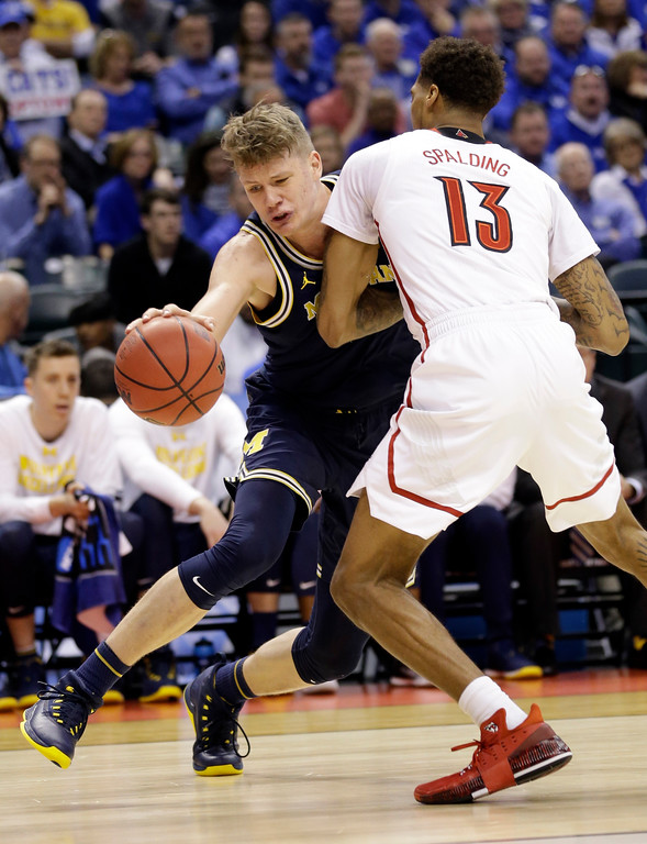 . Michigan forward Moritz Wagner (13) drives on Louisville forward Ray Spalding (13) during the second half of a second-round game in the men�s NCAA college basketball tournament in Indianapolis, Sunday, March 19, 2017. Michigan defeated Louisville 73-69. (AP Photo/Michael Conroy)