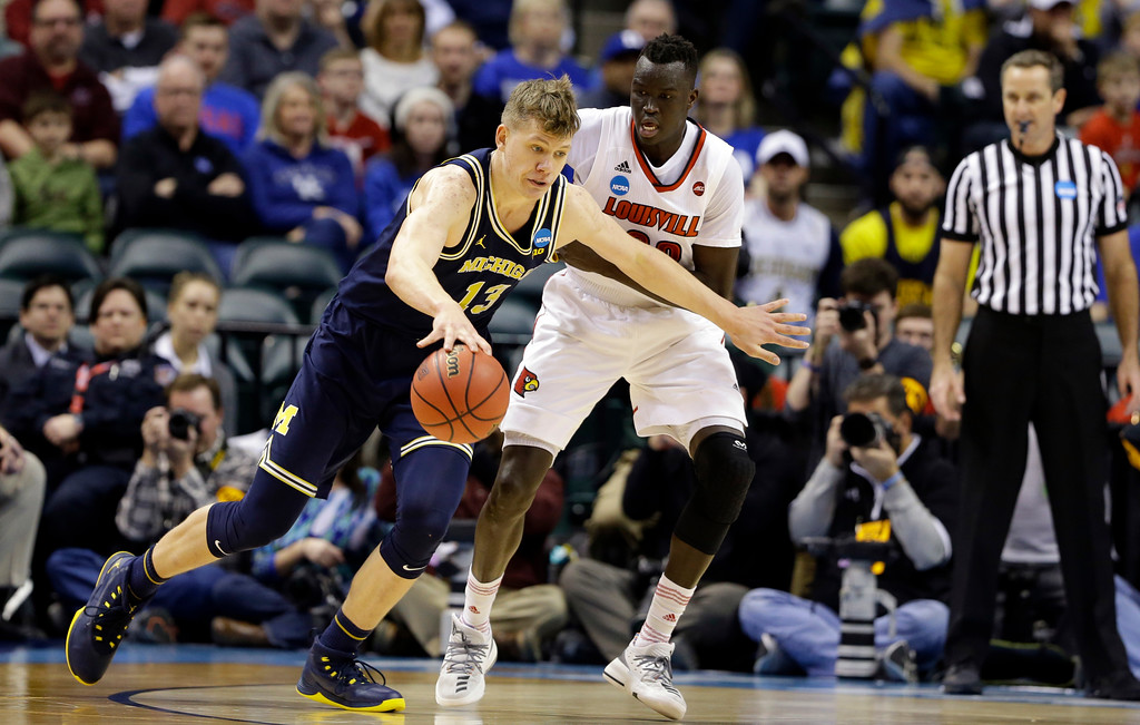. Louisville forward Deng Adel (22) defends Michigan forward Moritz Wagner (13) during the first half of a second-round game in the men�s NCAA college basketball tournament in Indianapolis, Sunday, March 19, 2017. (AP Photo/Michael Conroy)