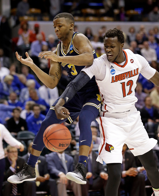. Louisville forward Mangok Mathiang (12) strips the ball from Michigan guard Xavier Simpson (3) during the first half of a second-round game in the men�s NCAA college basketball tournament in Indianapolis, Sunday, March 19, 2017. (AP Photo/Michael Conroy)