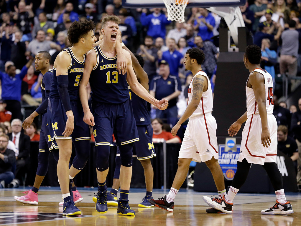 . Michigan forwards D.J. Wilson (5) and Moritz Wagner (13) celebrates during the second half of a second-round game against Louisville in the men�s NCAA college basketball tournament in Indianapolis, Sunday, March 19, 2017. Michigan defeated Louisville 73-69. (AP Photo/Michael Conroy)