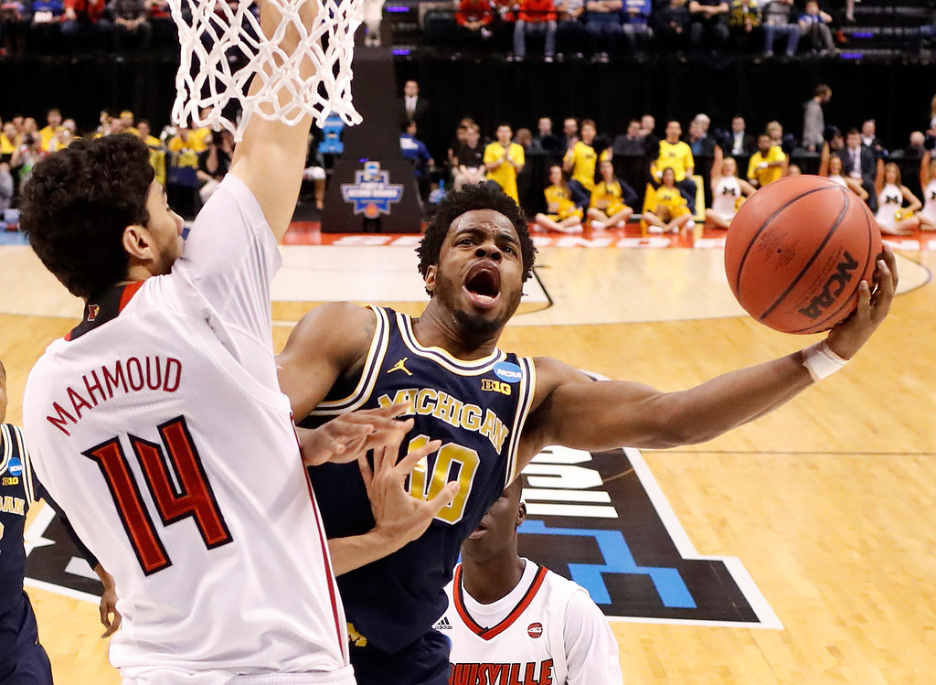 . Michigan\'s Derrick Walton Jr. (10) shoots as Louisville\'s Anas Mahmoud (14) defends during the first half of a second-round game in the men\'s NCAA college basketball tournament Sunday, March 19, 2017, in Indianapolis. (AP Photo/Jeff Roberson)