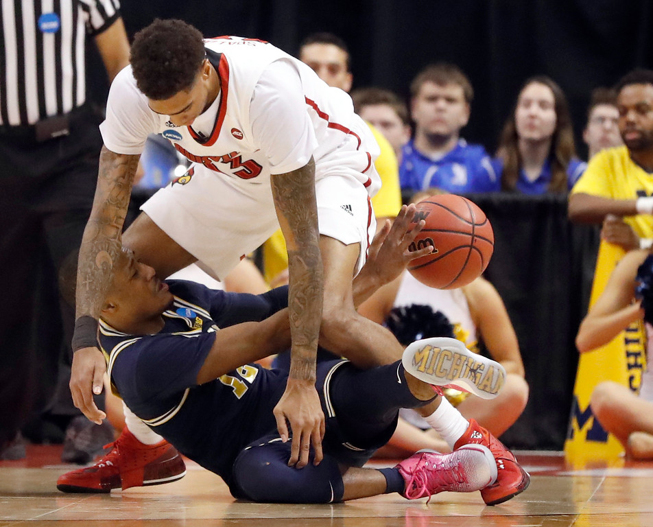 . Michigan\'s Muhammad-Ali Abdur-Rahkman, bottom, passes under Louisville\'s Ray Spalding during the second half of a second-round game in the men\'s NCAA college basketball tournament Sunday, March 19, 2017, in Indianapolis. Michigan won 73-69. (AP Photo/Jeff Roberson)