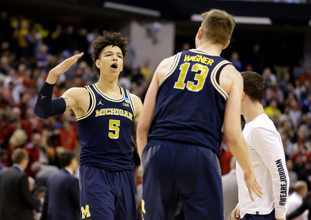 . Michigan forward Moritz Wagner (13) and forward D.J. Wilson (5) celebrates a 73-69 win over Louisville in a second-round game in the men�s NCAA college basketball tournament in Indianapolis, Sunday, March 19, 2017. (AP Photo/Michael Conroy)