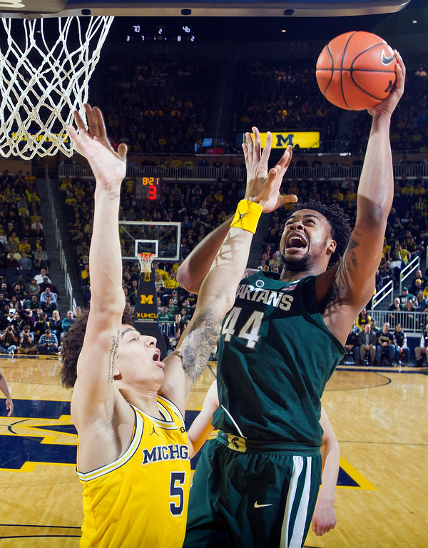 . Michigan forward D.J. Wilson (5) defends a shot attempt from Michigan State forward Nick Ward (44) in the second half of an NCAA college basketball game at Crisler Center in Ann Arbor, Mich., Tuesday, Feb. 7, 2017. Michigan won 86-57. (AP Photo/Tony Ding)