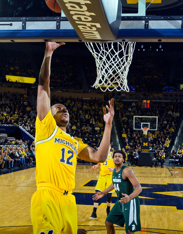 . Michigan guard Muhammad-Ali Abdur-Rahkman (12) makes a layup, watched by Michigan State forward Nick Ward (44), in the first half of an NCAA college basketball game at Crisler Center in Ann Arbor, Mich., Tuesday, Feb. 7, 2017. (AP Photo/Tony Ding)