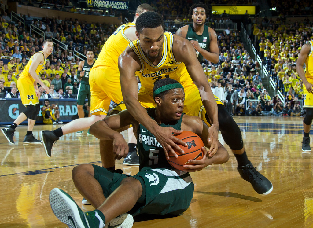 . Michigan State guard Cassius Winston, bottom, tries to keep the ball away from Michigan guard Zak Irvin (21), in the first half of an NCAA college basketball game at Crisler Center in Ann Arbor, Mich., Tuesday, Feb. 7, 2017. (AP Photo/Tony Ding)