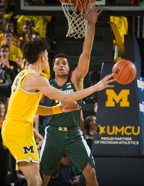 . Michigan State guard Miles Bridges, back, defends Michigan forward D.J. Wilson, left, in the first half of an NCAA college basketball game at Crisler Center in Ann Arbor, Mich., Tuesday, Feb. 7, 2017. (AP Photo/Tony Ding)