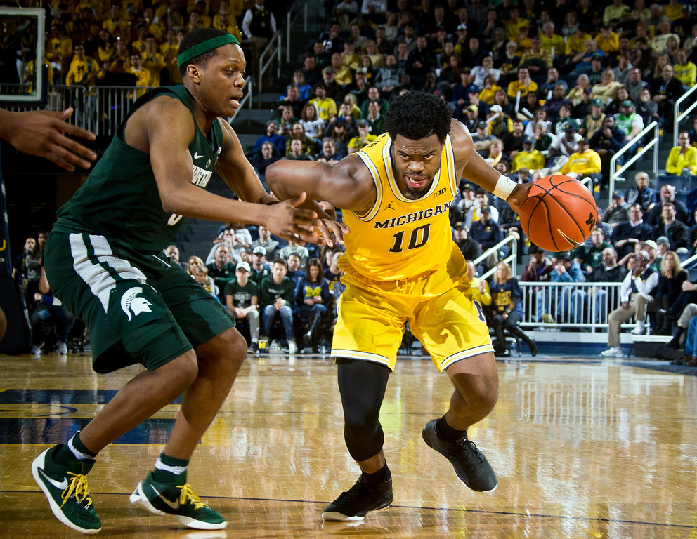 . Michigan State guard Cassius Winston (5) defends Michigan guard Derrick Walton Jr. (10) in the second half of an NCAA college basketball game at Crisler Center in Ann Arbor, Mich., Tuesday, Feb. 7, 2017. Michigan won 86-57. (AP Photo/Tony Ding)