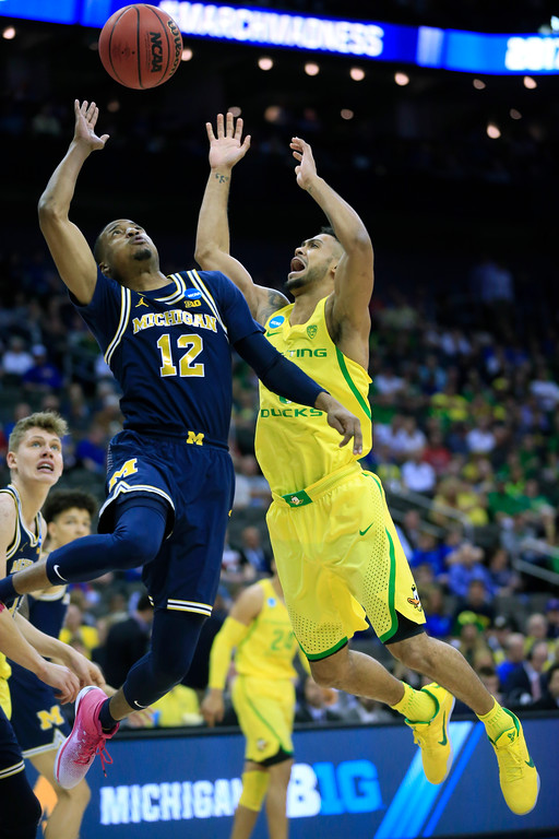 . Michigan guard Muhammad-Ali Abdur-Rahkman (12) shoots over Oregon guard Tyler Dorsey (5) during the first half of a regional semifinal of the NCAA men\'s college basketball tournament, Thursday, March 23, 2017, in Kansas City, Mo. (AP Photo/Orlin Wagner)