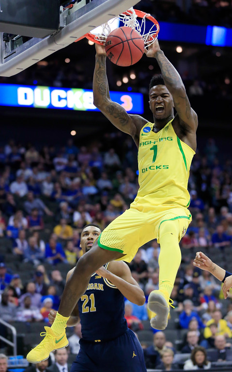 . Oregon forward Jordan Bell (1) dunks over Michigan guard Zak Irvin (21) during the first half of a regional semifinal of the NCAA men\'s college basketball tournament, Thursday, March 23, 2017, in Kansas City, Mo. (AP Photo/Orlin Wagner)
