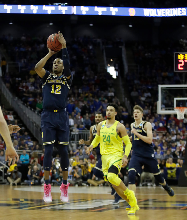 . Michigan guard Muhammad-Ali Abdur-Rahkman (12) shoots ahead of Oregon forward Dillon Brooks (24) during the first half of a regional semifinal of the NCAA men\'s college basketball tournament, Thursday, March 23, 2017, in Kansas City, Mo. (AP Photo/Charlie Riedel)